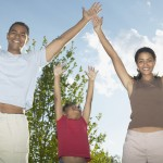 Portrait of a young couple and a child with their arms outstretched